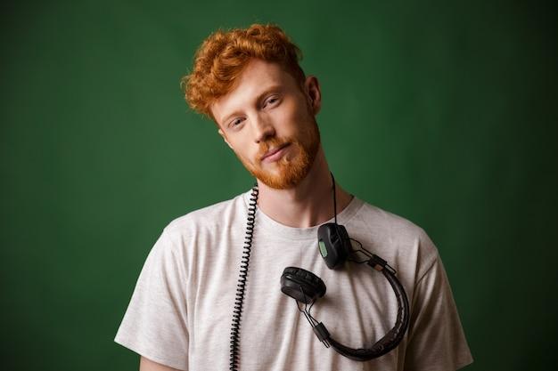 Knappe readheah bebaarde man in witte tshirt met koptelefoon