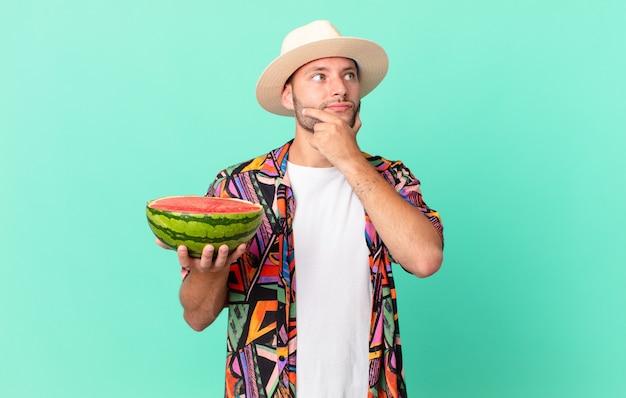 Knappe reiziger die denkt, zich twijfelachtig en verward voelt en een watermeloen vasthoudt. vakantie concept