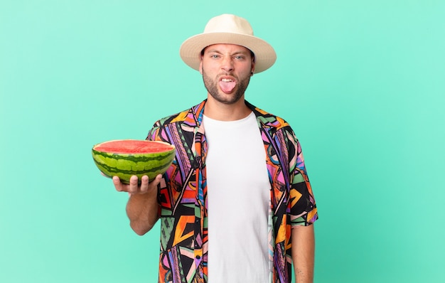 Knappe reiziger die walgt en geïrriteerd voelt en zijn tong uitsteekt en een watermeloen vasthoudt. vakantie concept