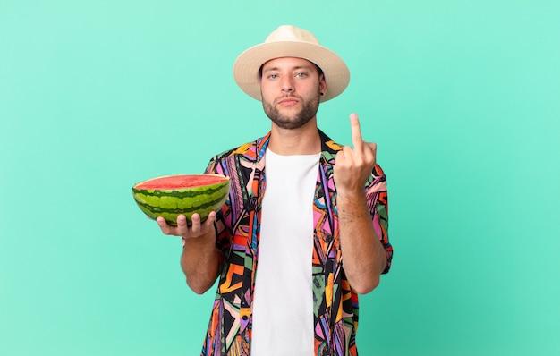 Knappe reiziger die zich boos, geïrriteerd, opstandig en agressief voelt en een watermeloen vasthoudt. vakantie concept