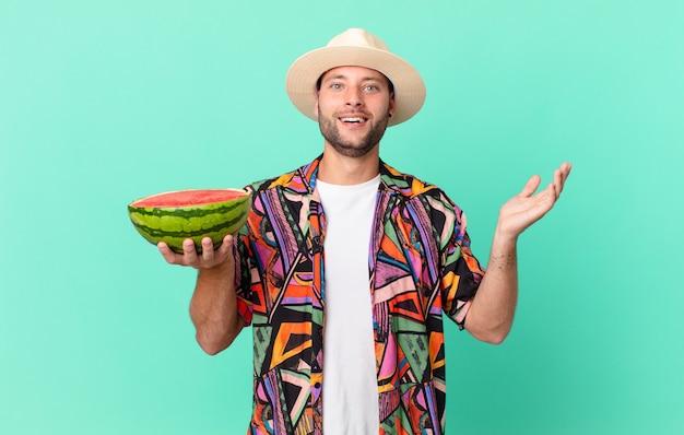 Knappe reiziger die zich gelukkig en verbaasd voelt over iets ongelooflijks en een watermeloen vasthoudt. vakantie concept