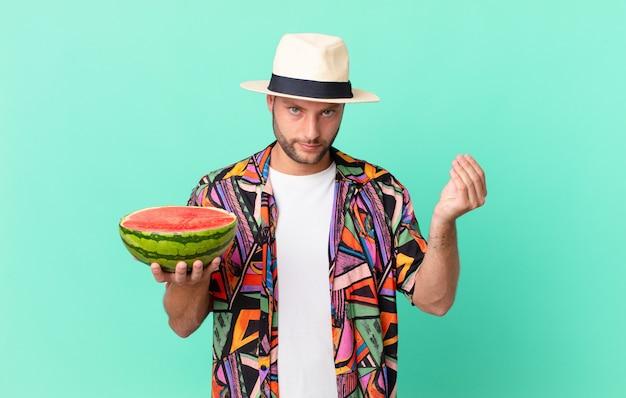 Knappe reiziger man die capice of geld gebaar maakt, zegt dat je moet betalen en een watermeloen vasthoudt. vakantie concept