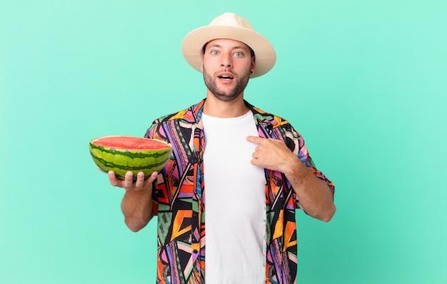 Knappe reiziger man die geschokt en verrast kijkt met wijd open mond, wijzend naar zichzelf en een watermeloen vasthoudend. vakantie concept