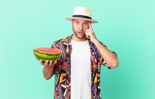 Knappe reiziger man die verrast kijkt, een nieuwe gedachte, idee of concept realiseert en een watermeloen vasthoudt. vakantie concept