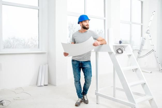 Knappe reparateur of bouwer in helm die met tekeningen werkt aan de renovatie van het interieur van een appartement