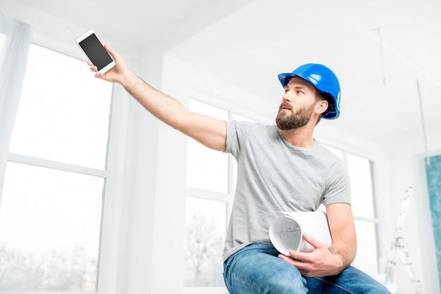 Knappe reparateur of bouwer in helm met telefoon en tekeningen in het witte interieur