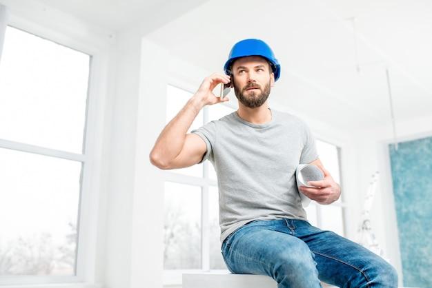 Knappe reparateur of bouwer in helm praten met telefoon met tekeningen in het witte interieur