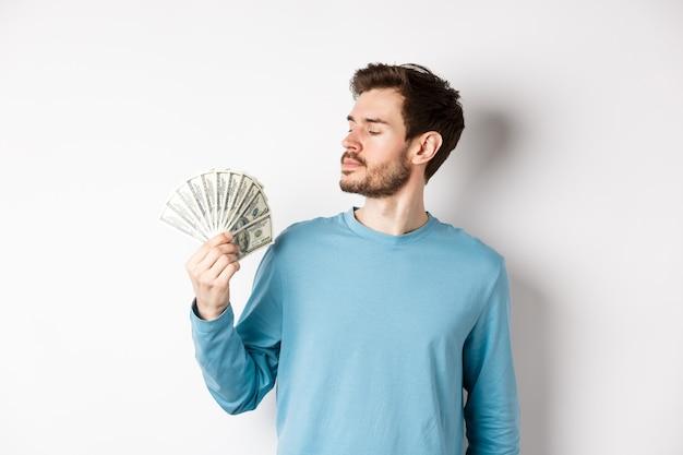 Knappe rijke man met baard kijken naar geld, kreeg snelle lening, staande op witte achtergrond.