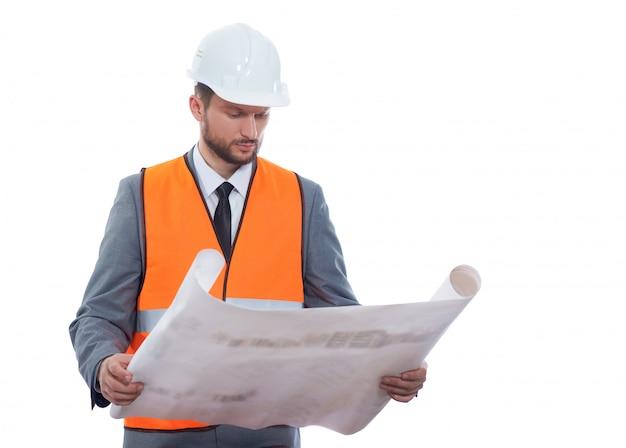Knappe rijpe gebaarde voorman in een formeel kostuum en veiligheidsvest die door de bouw van projectblauwdrukken gaan die op wit worden geïsoleerd