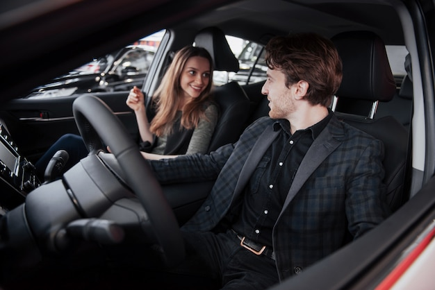 Knappe rijpe mens die bij zijn vrouw glimlachen terwijl samen het zitten in hun nieuwe auto