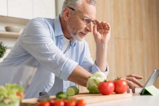 Knappe rijpe mens die glazen dragen die salade koken