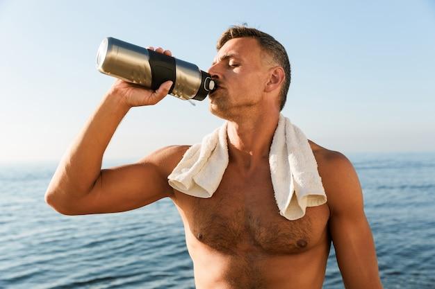 Knappe rijpe sportman met handdoek