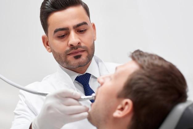 Knappe rijpe tandarts die zich tijdens het onderzoeken van tanden concentreert