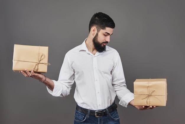 Knappe romantische kerel kijkt naar doos en maakt een keuze. het houden van een twee grote geschenkdoos voor zijn echtpaar, op grijs.