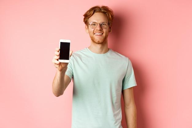 Knappe roodharige man in glazen met leeg smartphonescherm en glimlachen, demonstreren online promo of applicatie, staande over roze achtergrond.