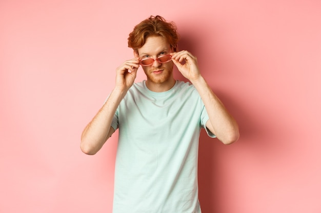 Knappe roodharige man in zomer zonnebril brutaal kijken naar camera, staande op roze achtergrond.