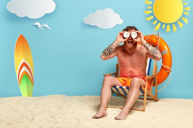Knappe roodharige poseren op het strand met zonnebrandcrème