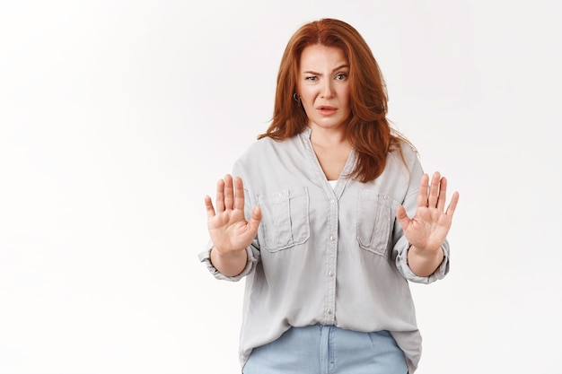 Knappe roodharige vrouw van middelbare leeftijd laat geen verbied gebaar zien handen opsteken defensief ineenkrimpen wenkbrauw optrekken verward staren minachting teleurstelling weigeren verdacht twijfelachtig aanbod