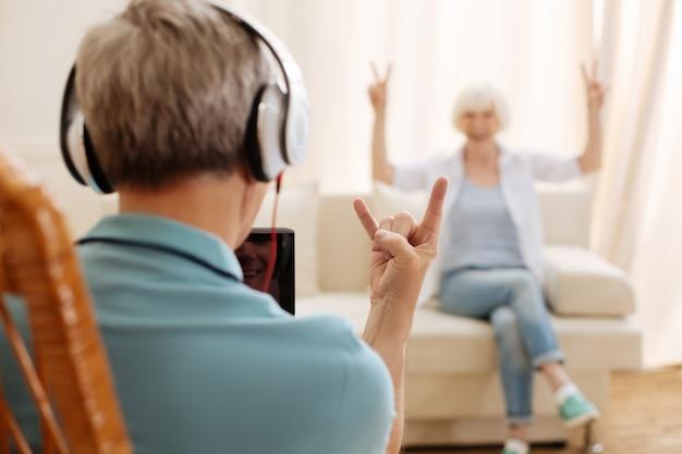 Knappe schattige hilarische heer die een koptelefoon draagt en zijn afspeellijst afspeelt terwijl hij plezier maakt met zijn vrouw