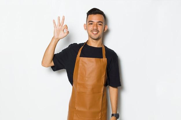 Knappe schort man glimlachend trots en blij met ok teken gebaar tumb omhoog geïsoleerd op witte achtergrond