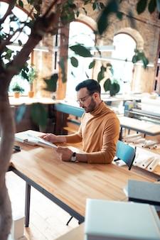 Knappe schrijver. bovenaanzicht van een knappe schrijver met een oranje polohals die aan de houten tafel zit