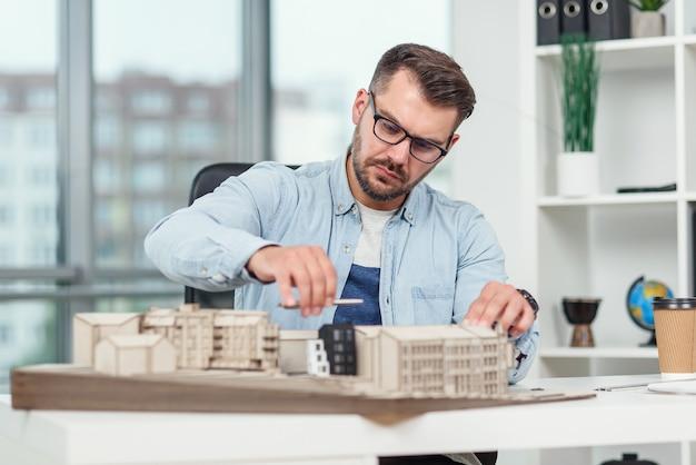 Knappe senior architect bij glazen bezig met een bouwproject en onderzoekt project van een wooncomplex waaraan hij werkt.