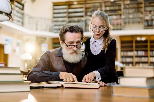 Knappe senior bebaarde grootvader leesboek samen met zijn schattige mooie kleindochter, wijzend op interessant moment in boek