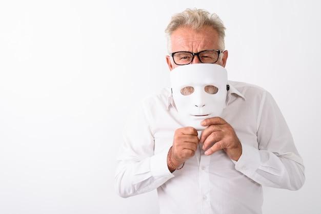 Knappe senior bebaarde man die mond bedekt met een wit masker terwijl hij een bril op wit draagt