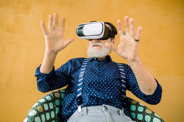 Knappe senior bebaarde man in stijlvolle hipster kleding, zittend op de stoel op gele achtergrond en genieten van film of spel in augmented reality-bril