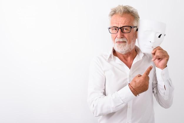 Knappe senior bebaarde man met wit masker in de buurt van gezicht en wijzende vinger terwijl het dragen van een bril op wit