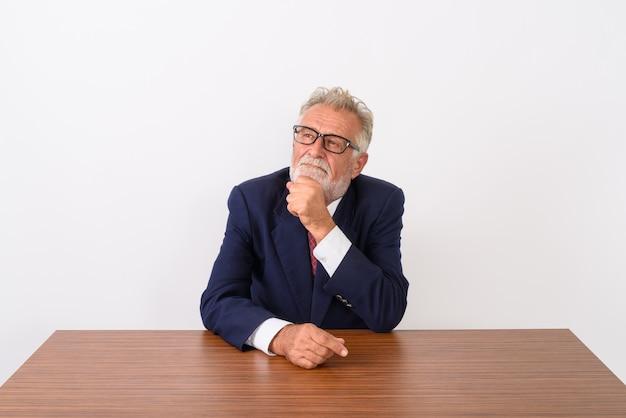 Knappe senior bebaarde zakenman denken zittend op houten tafel op wit