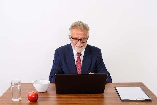 Knappe senior bebaarde zakenman met laptop zittend met fundamentele dingen voor werk op houten tafel op wit