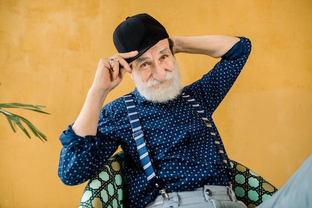 Knappe senior man in donkerblauw shirt, bretels en zwarte hipster cap poseren in studio, zit geel muur. stijlvolle modieuze oudere man op gele achtergrond
