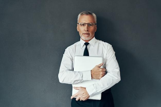 Knappe senior man in elegant overhemd en stropdas die laptop draagt en naar de camera kijkt terwijl hij tegen een grijze achtergrond staat