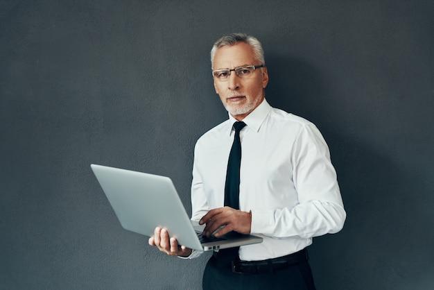 Knappe senior man in elegant overhemd en stropdas die laptop gebruikt en naar de camera kijkt terwijl hij tegen een grijze achtergrond staat