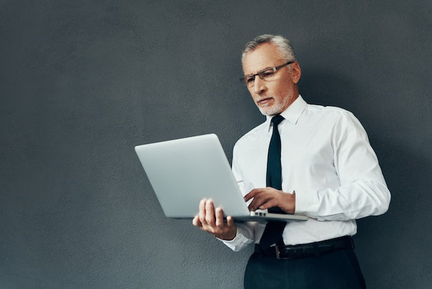 Knappe senior man in elegant overhemd en stropdas die laptop gebruikt terwijl hij tegen een grijze achtergrond staat