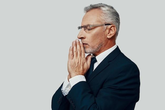 Knappe senior man in volledig pak die handen ineengeklemd houdt terwijl hij tegen een grijze achtergrond staat