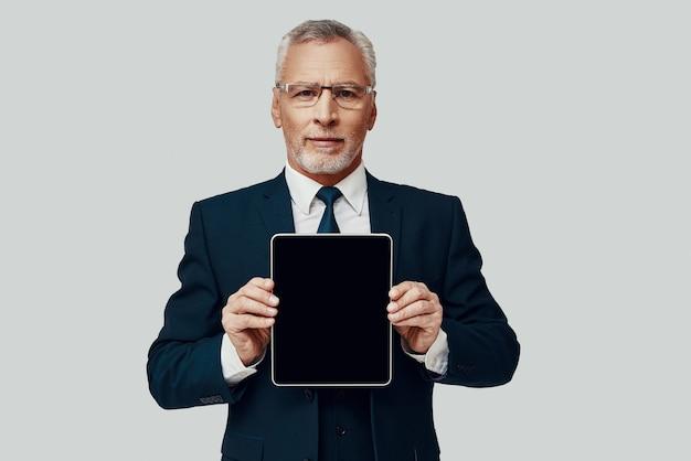 Knappe senior man in volledig pak die kopieerruimte op digitale tablet wijst en glimlacht terwijl hij tegen een grijze achtergrond staat