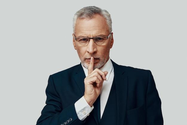 Knappe senior man in volledig pak die naar de camera kijkt en de vinger op de lippen houdt terwijl hij tegen een grijze achtergrond staat