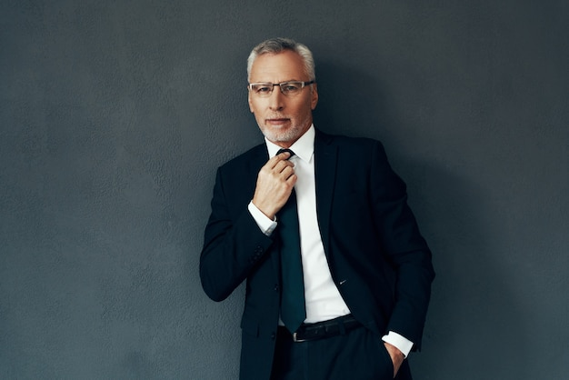 Knappe senior man in volledig pak die naar de camera kijkt en stropdas aanpast terwijl hij tegen een grijze achtergrond staat