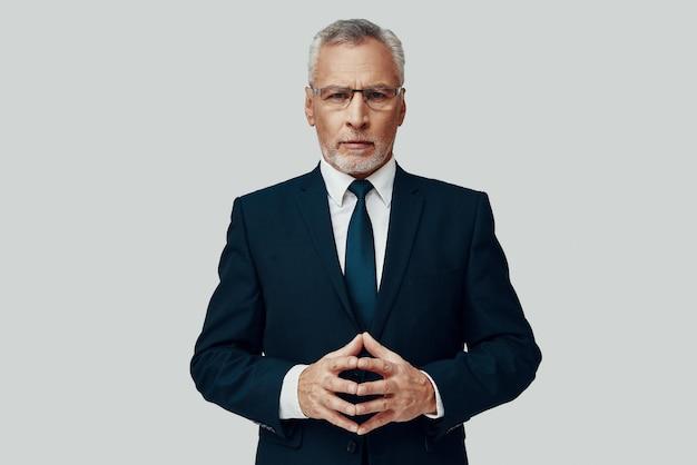 Knappe senior man in volledig pak die naar de camera kijkt en zijn handen gevouwen houdt terwijl hij tegen een grijze achtergrond staat