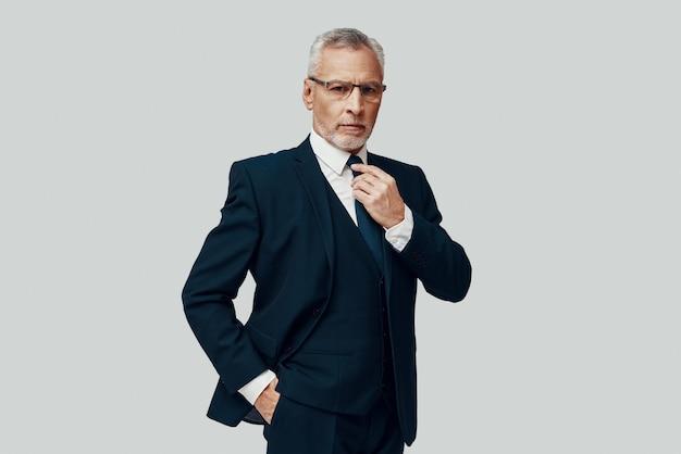 Knappe senior man in volledig pak die naar de camera kijkt en zijn stropdas aanpast terwijl hij tegen een grijze achtergrond staat