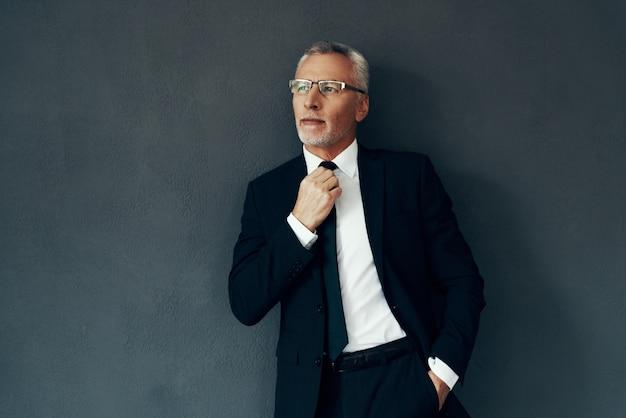 Knappe senior man in volledig pak die wegkijkt en stropdas aanpast terwijl hij tegen een grijze achtergrond staat
