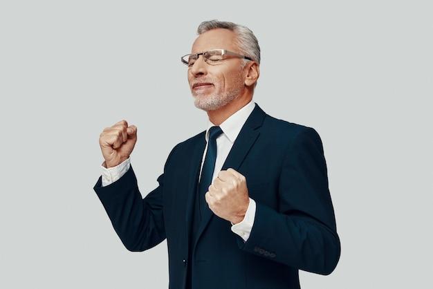 Knappe senior man in volledig pak gebaren en juichen terwijl hij tegen een grijze achtergrond staat