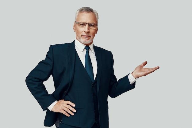 Knappe senior man in volledig pak kijkend naar camera en wijzend op kopieerruimte terwijl hij tegen een grijze achtergrond staat