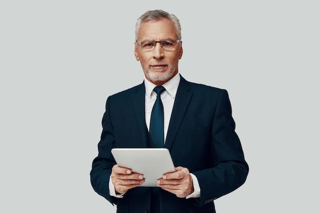 Knappe senior man in volledig pak met behulp van digitale tablet en kijkend naar een camera terwijl hij tegen een grijze achtergrond staat