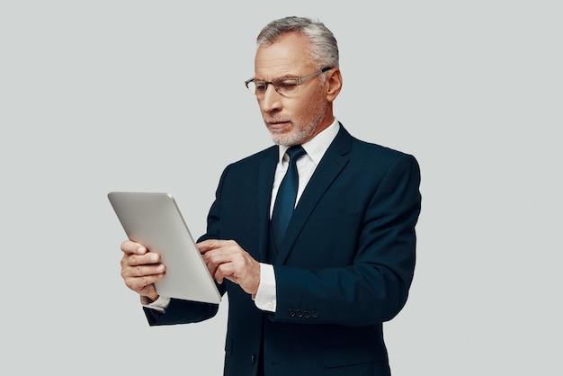 Knappe senior man in volledig pak met behulp van digitale tablet terwijl hij tegen een grijze achtergrond staat