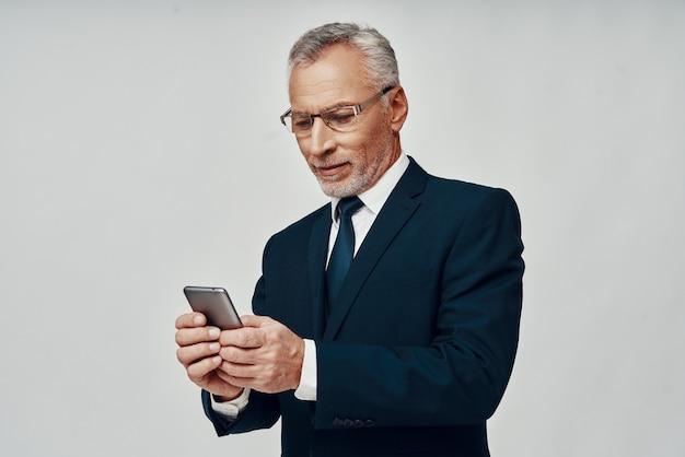 Knappe senior man in volledig pak met behulp van slimme telefoon en glimlachend terwijl hij tegen een grijze achtergrond staat