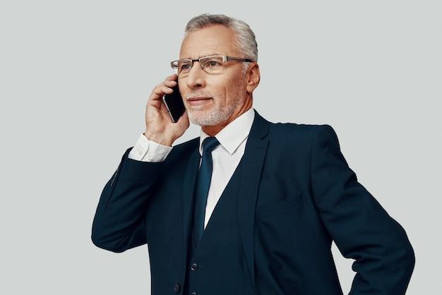 Knappe senior man in volledig pak praten aan de telefoon terwijl hij tegen een grijze achtergrond staat