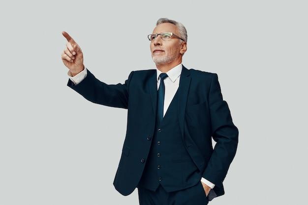 Knappe senior man in volledig pak wijzend op kopieerruimte terwijl hij tegen een grijze achtergrond staat
